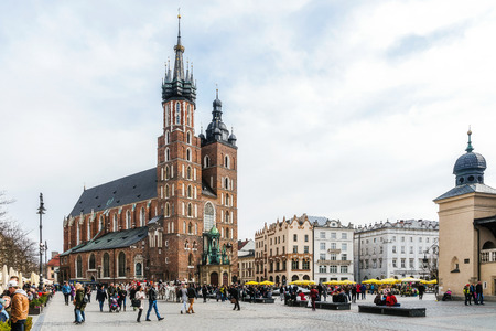 KRAKOW, POLAND - MARCH 25, 2017: Old Market Square crowded with tourists at the St. Marys Basilica, brick Gothic church built in the early 13th century is the main landmark of the city.