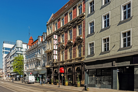 GLIWICE, POLAND – MAY 1, 2017: Main street view with the tenement being an interesting example of modernism style. Characteristic rounded corner is filled with milk glass which is illuminated at night