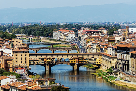FLORENCE, ITALY – AUGUST 8, 2017: The Ponte Vecchio (Old Bridge), a medieval stone bridge over the Arno River having shops belonging to jewelers, art dealers and souvenir sellers built along it.