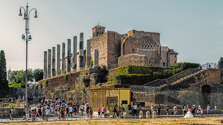 ROME – AUGUST 10, 2017: Tourists pass by The Temple of Venus and Roma, the largest temple in Ancient Rome designed by the emperor Hadrian in 121. And completed in 141 under Antoninus Pius.
