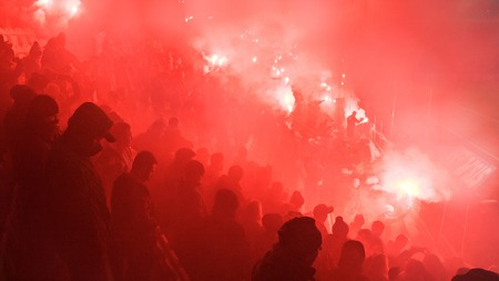 KRAKOW, POLAND-DECEMBER 13, 2017: Polish soccer fans lighting smoke flares at Cracovia Stadium, during the Polish Premiere League match Cracovia vs Wisla Krakow, in Krakow
