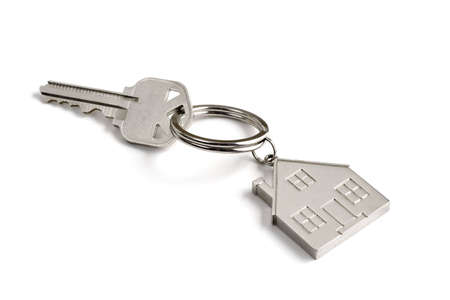 A metal key with a little house key ring on a white background Фото со стока