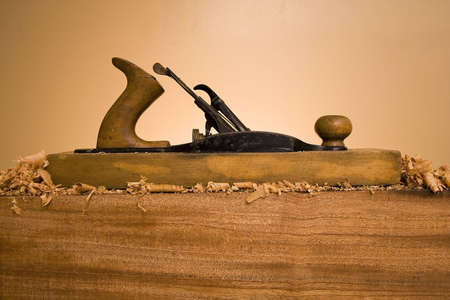 An old wood plane hand tool on a wooden block with wood shavings and saw dust. Archivio Fotografico