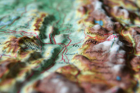 A macro photo of Topographic Map relief map with a focus on a valley town surrounded by mountains Stock Photo