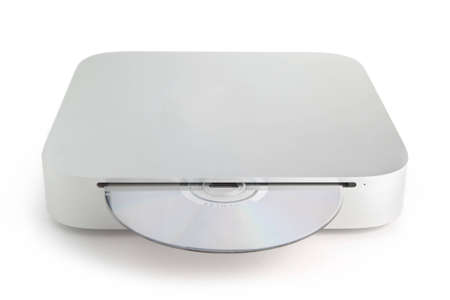 A mini computer on a white background with a CD disc in the front CD drive Stock Photo