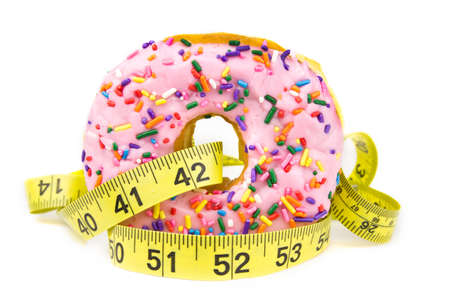 A pink frosted donut with colorful sprinkles with a yellow diet measuring tape wrapped around it isolated on a white background