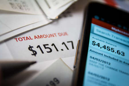 A selective focus shot of a pile of bills and receipts with a smart phone with an account balance displayed on the screen
