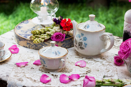 teaset: English classic tea set in the garden table with pink petals Stock Photo