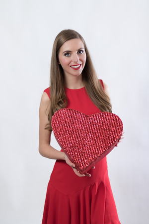 young woman in a red dress holding a heart photo