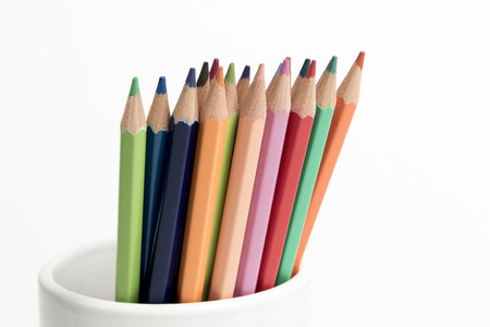 A group of multi colored pencils in a white cup on an isolated background 스톡 콘텐츠
