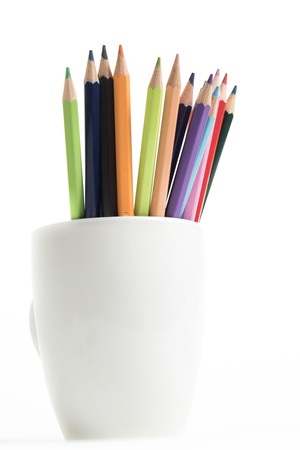 A group of multi colored pencils in a white cup on an isolated background Imagens