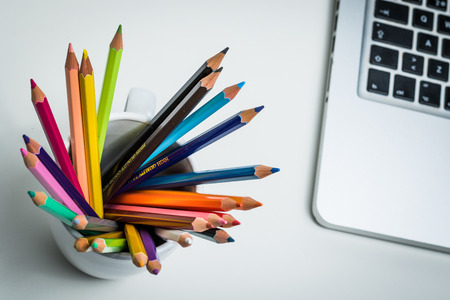 A group of color pencils and a laptop computer in a creative workspace