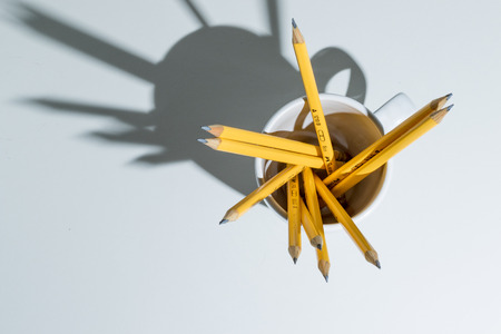 A group of yellow pencils in a white cup from top casting strong shadows on a white background