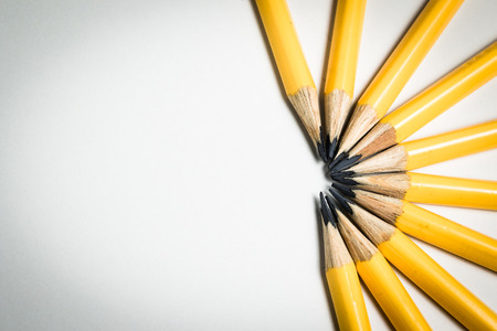 A group of yellow pencils aiming to one direction as a conceptual image of team, leadership, competition.