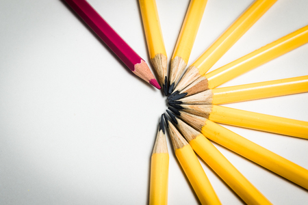 A red pencils standing out from a group of yellow pencils