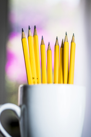 A group of yellow pencils in a white cup with a blurred background