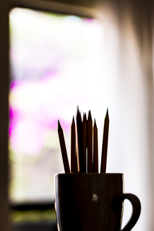 A group of color pencils in shadows in a silhouette cup with a blurred window and garden background 스톡 콘텐츠