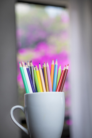 A group of color pencils on a blurred window background