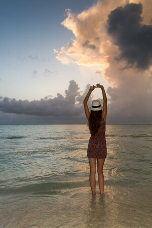 A young woman enjoying the sunset at the seashore at the Caribean Sea near Cancun Mexico