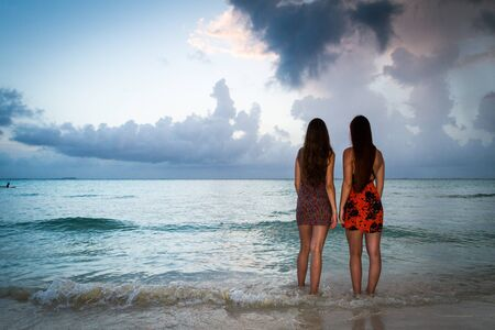 Two young girls enjoying the seaside at the Caribean sea near Cancun Mexico Stock Photo