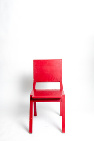 Single red modern chair in a white isolated background