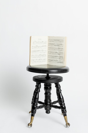Old antique black stool with a round seat from a piano Imagens