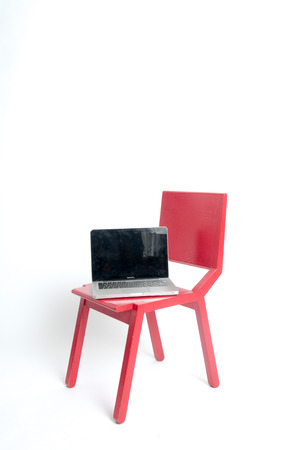 Modern designer red chair with a laptop in a white isolated background