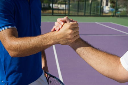Two men professional tennis players shake hands before and after the tennis match