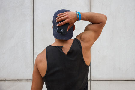 strong: Young, caucasian, strong and handsome man wearing a black tank top and turns His back. I wears a cap on and I Have the phone in hand. I shows his biceps.
