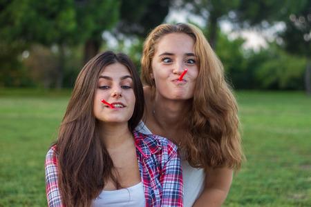 amigas comiendo regaliz rojo mientras disfruta de unas vacaciones en el parque. Son jóvenes, uno tiene los ojos azules y el otro es rubio.