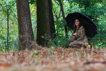 umbrela: Young girl walking on a path in a forest a rainy day. She goes With an umbrella Against the rain. The forest is very colorful.