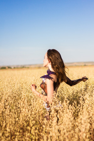 half naked: Girl makeup with body paint walking half naked through a field of wheat a sunny summer day.