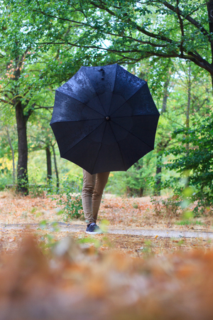 umbrela: Young caucasian girl enjoying a rainy day in the countryside .. She goes With an umbrella Against the rain. The forest is very colorful.