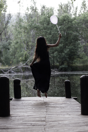 sinister: Girl in a black dress holding a globe in her hand is above the jetty looking towards the lake in a sinister forest. Stock Photo