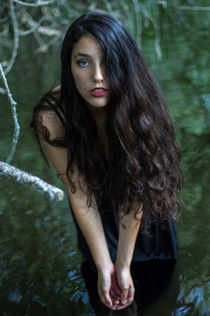 Pretty girl with black hair bathing in a lake of a pretty but sinister forest. She is wearing a black dress.