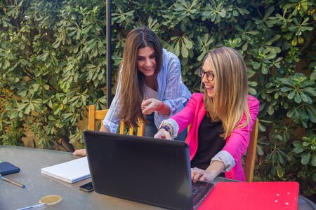 jovenes emprendedores: Young entrepreneurs working with a laptop. They are two beautiful Caucasian girls Who are creating Their company. They work on the terrace of Their house. Foto de archivo