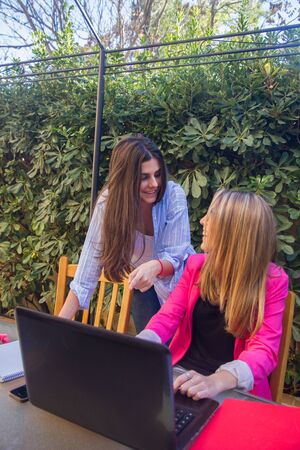 jovenes empresarios: Young entrepreneurs working with a laptop. They are two beautiful Caucasian girls Who are creating Their company. They work on the terrace of Their house. Foto de archivo