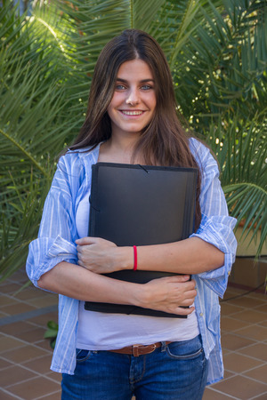 Young blue eyed entrepreneur with a folder with documents in her arms. She is cheerful and dressed smart Because she is going to work. Stock Photo