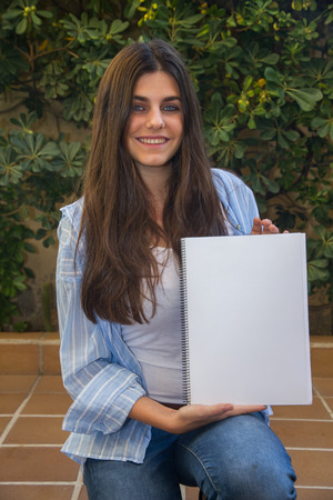 Pretty white girl with blue eyes entrepreneur holding a blank notebook With her hands Where you can enclose a text, an image or an outline. Stock Photo
