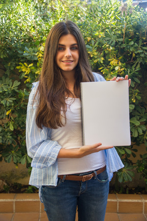 enclose: Pretty white girl with blue eyes entrepreneur holding a blank notebook With her hands Where you can enclose a text, an image or an outline. Stock Photo