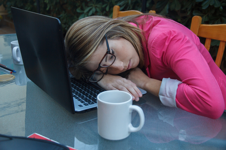 too much work: Young girl tired of entrepreneurial working so much, she falls asleep on top of the laptop on the table. She is a business woman with too much work.