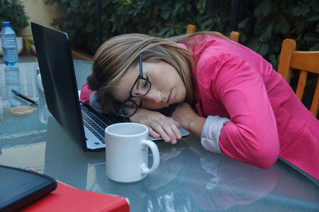 Young girl tired of entrepreneurial working so much, she falls asleep on top of the laptop on the table. She is a business woman with too much work.