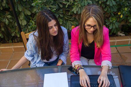 jovenes emprendedores: Los jóvenes empresarios que trabajan con un ordenador portátil. Son dos hermosas niñas de raza blanca que están creando su compañía. Trabajan en la terraza de su casa.