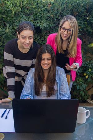 jovenes empresarios: Los jóvenes empresarios que trabajan con un ordenador portátil. Son tres hermosas niñas raza blanca, de la creación de su empresa. Trabajan en la terraza de su casa. Foto de archivo