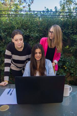 jovenes emprendedores: Los jóvenes empresarios que trabajan con un ordenador portátil. Son tres hermosas niñas raza blanca, de la creación de su empresa. Trabajan en la terraza de su casa. Foto de archivo
