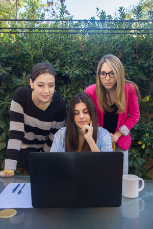 jovenes emprendedores: Young entrepreneurs working with a laptop. They are three beautiful Caucasian girls Who are creating Their company. They work on the terrace of Their house.