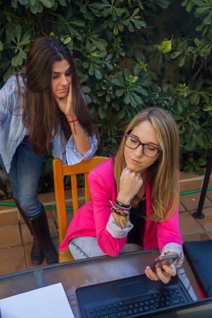 jovenes empresarios: Los jóvenes empresarios que trabajan con un ordenador portátil. Son dos hermosas niñas de raza blanca que están creando su compañía. Trabajan en la terraza de su casa.