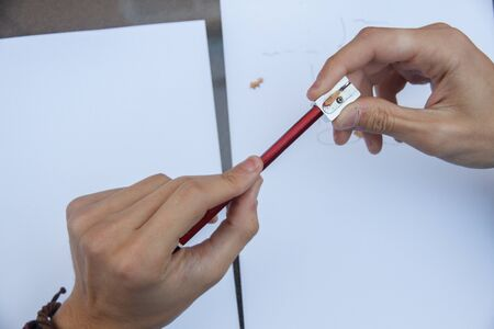 pencil point: Photo of close up of a hands pulling a pencil point to continue writing on a table.