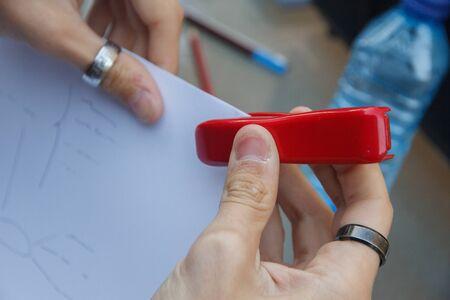 engrapadora: Foto de cerca de una persona con un documentos grapadora de grapado en una mesa.