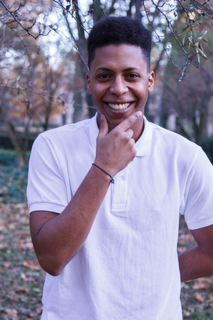 Handsome young black man with confidence in himself having a good time in the park on an autumn day.